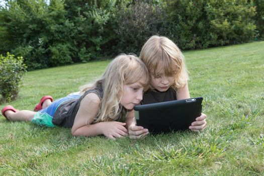 Two blond boys are lying on the lawn and are looking to the tablet.