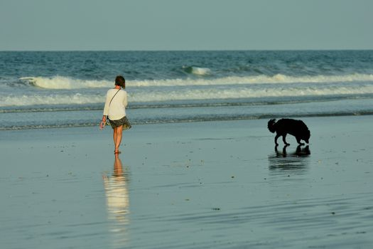 An unidentified young woman enjoying a walk on the beach, with her dog exploring the beach.