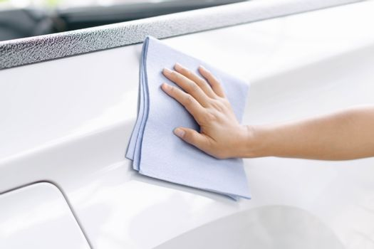 Man cleaning car with microfiber cloth, car detailing (or valeti
