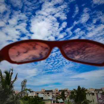 Chennai, India - July 3 2020: Red color glass placed in wall to see beautiful view of the sky from the glass lens and foreground view of buildings