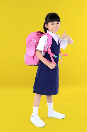 Back to school. Portrait of happy asian cute little child girl in uniform with school bag smiling  show finger thumb up when go back to school, isolated orange background.