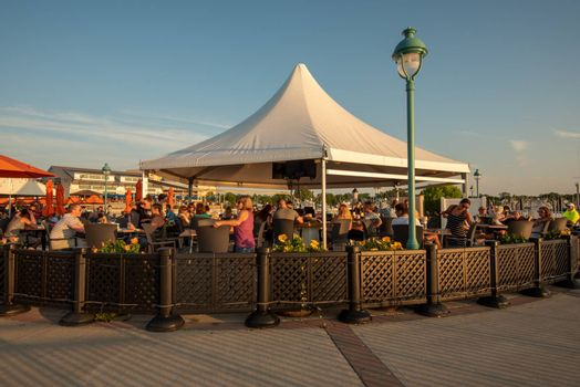 Belmar, NJ, USA -- July 19, 2017. A wide angle photo of people enjoying outdoor cocktails and dining on the waterfront at the Belmar Marina.