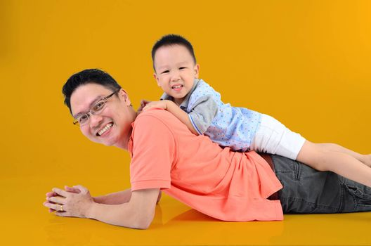 Happy father's day! joyful young dad  playing with  his cute son. Father giving young boy piggyback ride on floor at home. Isolated on orange background.