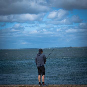 Barnegat, NJ, USA -- September 13, 2019. Photo of a young man fishing in Barnegat Bay from the boardwalk in Barnegat, NJ.
