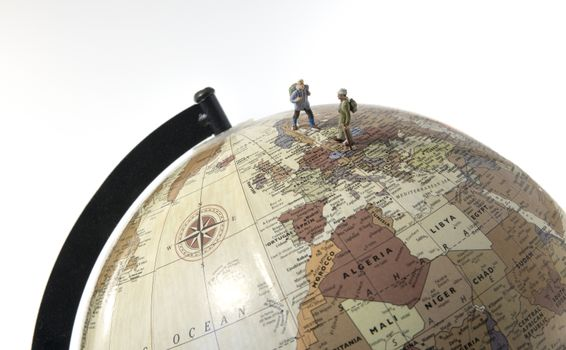 little figures backpaking europea as a big adventure with backpack and walking on a globe
