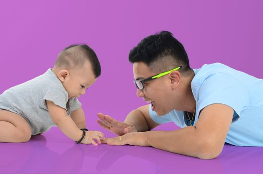 Happy father's day! joyful young dad  playing with  his cute son and lying on floor at home. Isolated on purple background.