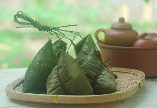 Chinese tradition food - Chinese Steamed Rice Dumpling  with green background outdoor.Zongzi or traditional chinese sticky rice dumpling usually taken during festival occasion.