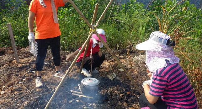 Group of asian hiking girl cooking in a black pot on around a bonfire at outdoor forest.