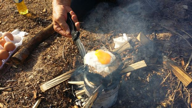 person cooking fried eggs in nature camping outdoor, cooker prepare breakfast scrambled picnic on metal stove.