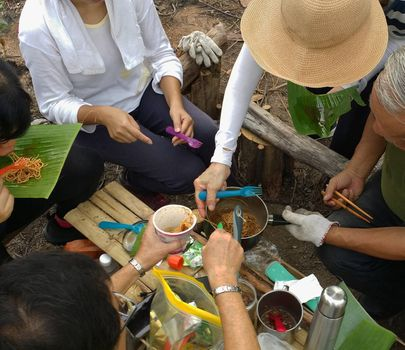 Directly above view of hiker's having breakfast at wooden table with noodles coffee and other meals at the forest camp. People camping at national park and doing picnic lunch outdoors.