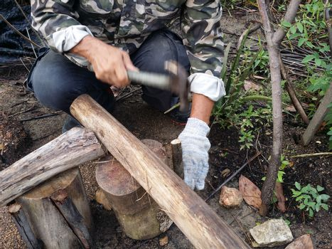 A man hammer a tree with a hammer and  nail for making a chair at garden.