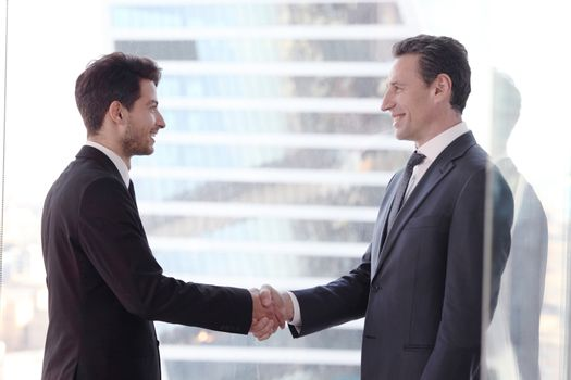 Business people shaking hands by the window in office