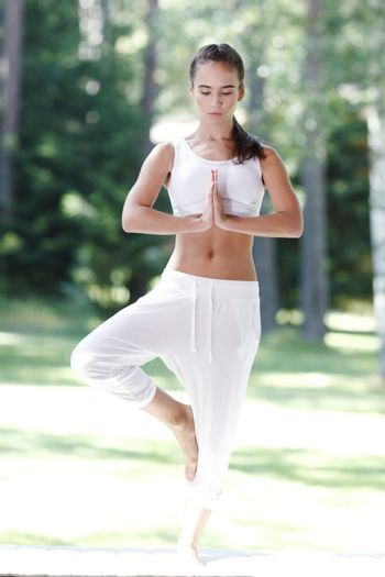 Young woman in white sportswear doing yoga exercise outdoors