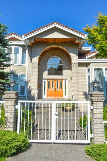 Entrance of luxury family house with white gates in front. Vancouver, Canada