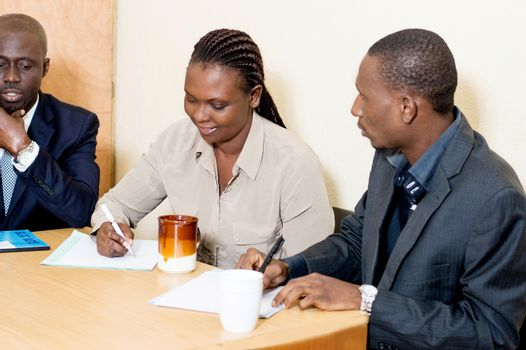 Young woman smiling takes notes at a business meeting while two men at her side looks at her writing