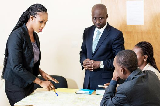 Young businesswoman shows her colleagues the different ways on the card placed in front of them