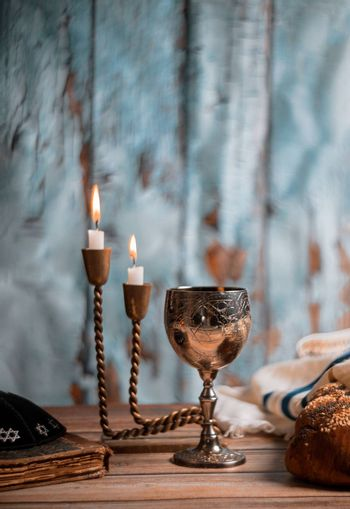 Shabbat Jewish holiday with challah bread on a candles and cup of wine.