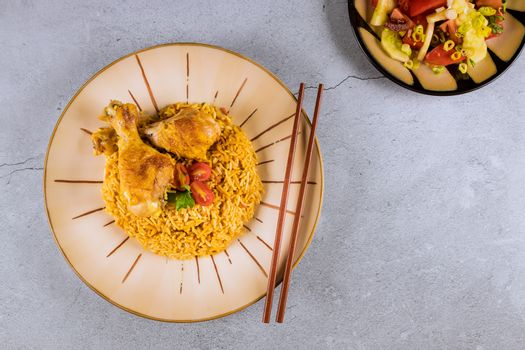Chicken breast with fried rice chinese cuisine on a plate with chopsticks
