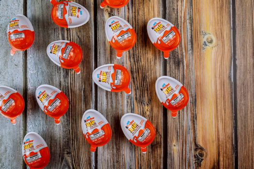 New York NY NOV 08 2019:Kinder Surprise eggs on old wooden background. Word Surprise written in manufactured by Italian company Ferrero.