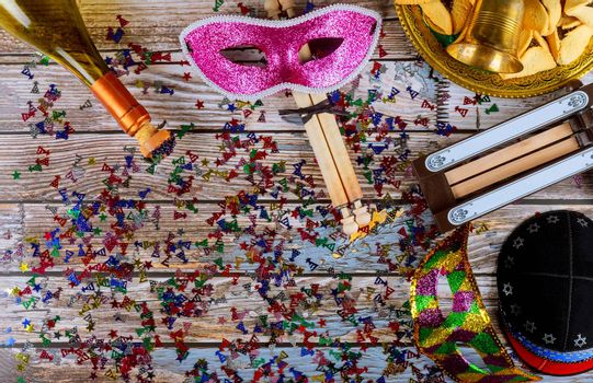 Purim traditional with hamantaschen cookies, noisemaker and carnival mask on old wood background