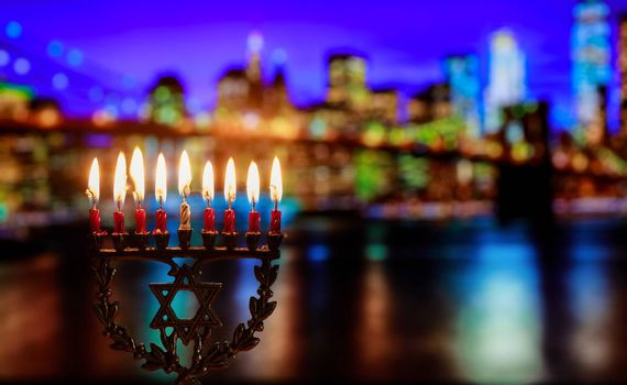 Chanukah menorah symbol of traditional jewish holiday Brooklyn Bridge over night New York City with lights