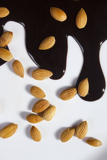 Almonds and melted chocolate on a white background