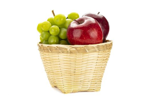 A bunch of green grapes and red apples in a weave bamboo basket. Isolated on white background.