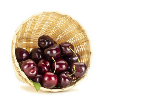 A bunch of ripe red cherries in a weave bamboo basket. Isolated on white background.