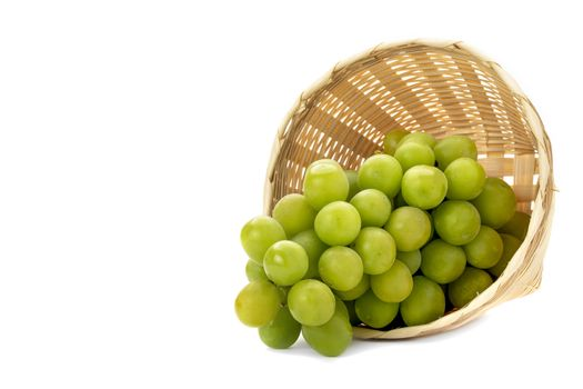 A bunch of green grapes in a weave bamboo basket. Isolated on white background.