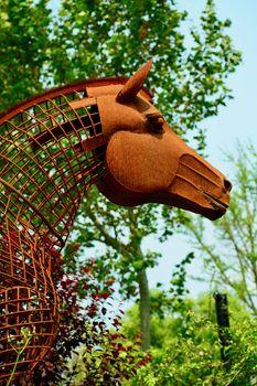 Modern sculpture made of rusty wire; a garden sculpture representing a horse