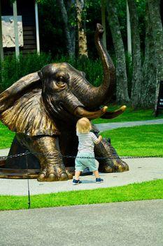 Modern sculpture, a little child, a bronze elephant
