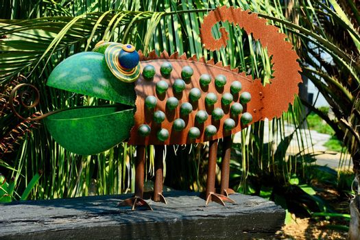 Funny garden sculpture representing a chameleon. Glass and rusty metal as its building elements.