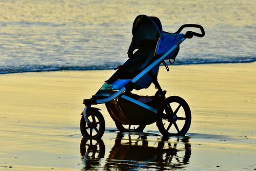 A baby carriage left on a beach; sea waves touching the wheels.