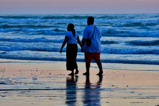 Unidentified people enjoying sunset on a beach.