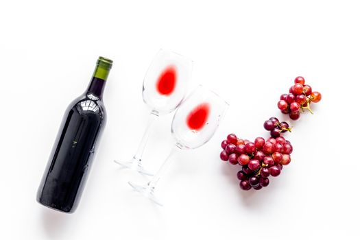Red wine with grape - in glasses and bottle - on white desk top view
