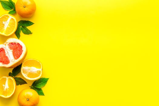 Oranges and grapefruits with leaves on table top view copy space