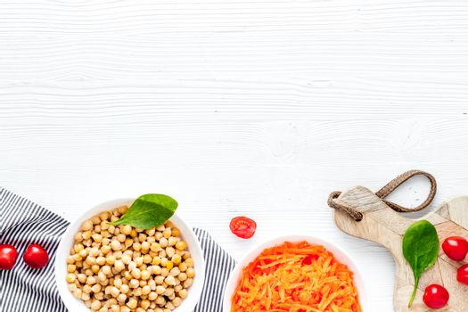 Vegetarian bowl with chickpeas and vegetables - white table top view copy space