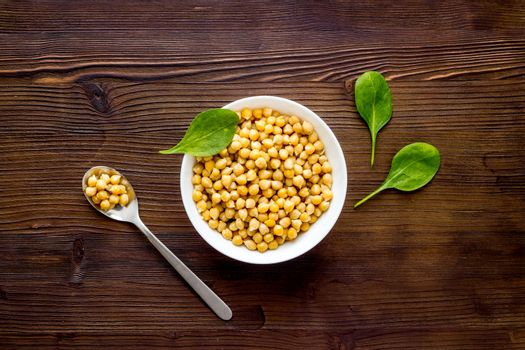 Raw chickpeas in bowl on wooden kitchen table top view