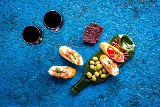 Red wine and snacks set on wine bottle plate top view