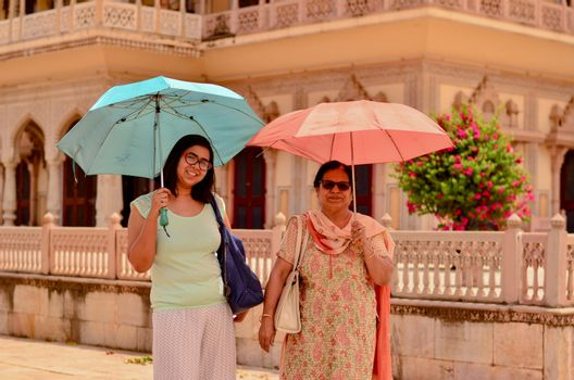 Happy looking young and old (mother - daughter) tourists posing in Jaipur's City Palace with umbrellas matching their outfits in City Palace, Jaipur, Rajasthan, India