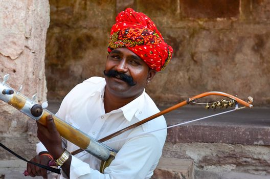 Jodhpur, Rajasthan, India, 2020. Closeup of Traditional Rajasthani sarangi player in his traditional dress and head gear turban red pagdi playing sarangi in Mehrangarh Fort.