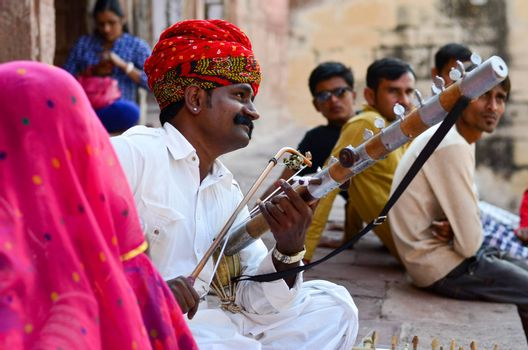 Jodhpur, Rajasthan, India, circa 2020. Sarangi player performing in his traditional dress and head gear pagdi in Rajasthan as tourists enjoys his performance in Mehrangarh Fort.
