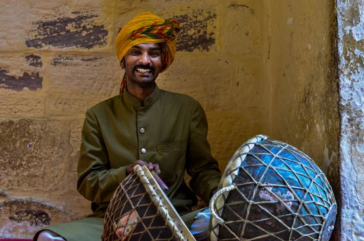 Jodhpur, Rajasthan, India, 2020. Traditional Rajasthani drum player wearing yellow pagdi playing drums in Mehrangarh Fort.
