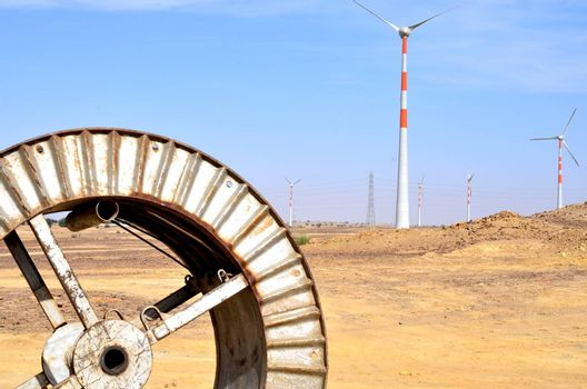 Windmills in the backdrop of a winding wheel on the way to Sam Sand Dunes (Thar Desert) from Jaisalmer, Rajasthan, India. The Jaisalmer Wind Park is India's 2nd largest operational onshore wind farm.