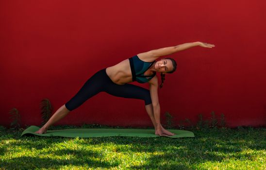 Beautiful Sportive Woman Doing Yoga Exercise Outdoors. Morning Workout Near the Home. Healthy Lifestyle. Utthita Parsvakonasana. Extended Side Angle Pose