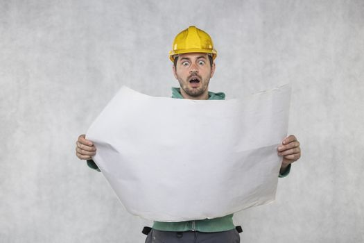 the frightened builder looks at plans to build a house