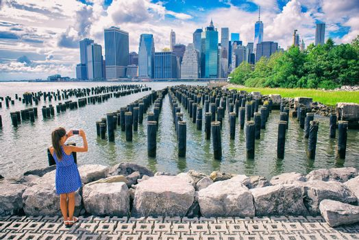 New York tourist woman taking mobile picture with smartphone. Manhattan city skyline waterfront lifestyle. People walking enjoying view of downtown from the Brooklyn bridge park Pier 1 salt marsh