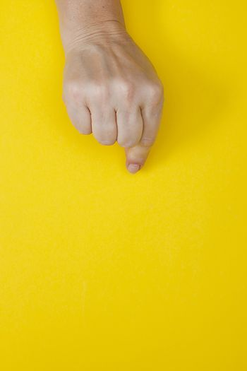 Hand with clenched fingers in a pinch on a yellow background