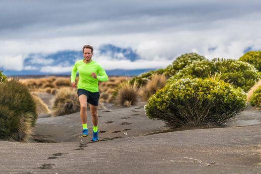 Trail run man athlete runner running marathon in desert landscape mountain hills summer background. Fitness and sports lifestyle.