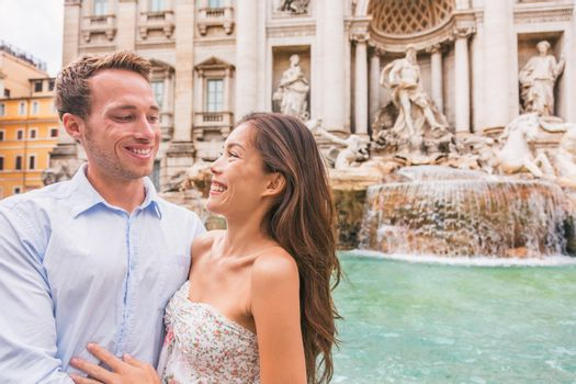 Rome couple on romantic date by Trevi Fountain in Roma, Italy. Romantic luxury honeymoon Europe cruise travel tourists lovers traveling in european city. Asian woman falling in love with Italian man.
